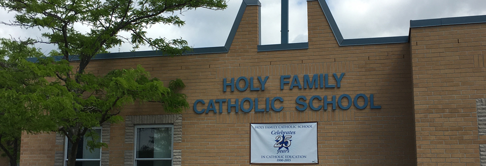 "Exterior of Holy Family Catholic School with banner saying, ""Holy Family Catholic School Celebrates 25 years in Catholic education""."